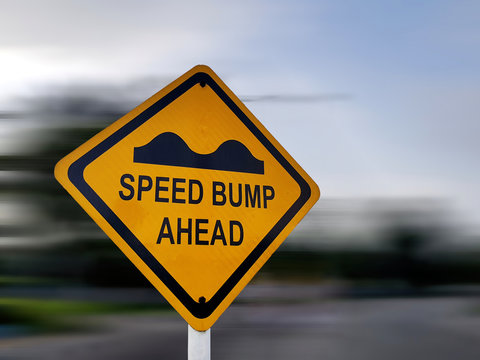 Speed Bump Sign - Yellow Road Traffic Warning Sign, on a Speeding Blurred Background