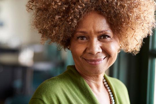 Portrait Of Smiling Senior Woman Sitting In Restaurant