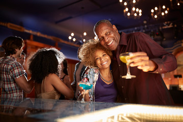 Portrait Of Senior Couple Drinking And Dancing In Bar Together