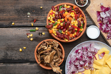 Mixture of vegetables, dried boletus mushrooms, sliced potato, red onion sliced and whole on a cutting board and spices, on old rustic wooden table. With copy space.