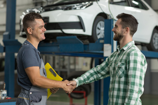 Smiling worker of car service in uniform and satisfied client shaking hands. Happy man in checkered shirt thankful mechanic for repaired automobile. Concept of dealing and agreement.