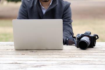屋外でパソコンを操作する男性カメラマン