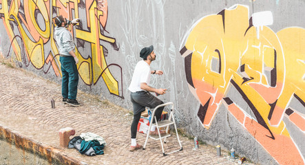 Graffiti artists friends painting with color spray on the wall for international competition - Focus on right guy face