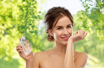 perfumery, beauty and luxury concept - happy smiling young woman smelling perfume from her wrist over green natural background