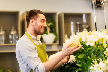 small business, sale and floristry concept - florist or seller with white lilies at flower shop