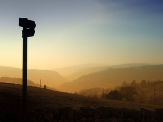 a direction sign in silhouette pointing down a glowing evening sunset valley with golden tree covered hills vanishing into the distance against a blue twilight sky