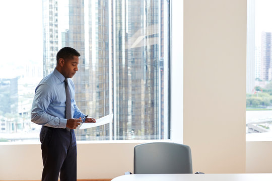 Mature Businessman Standing Rehearsing Before Giving Presentation In Modern Open Plan Office