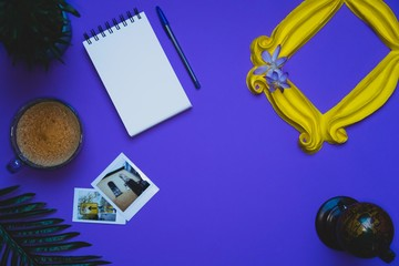 Purple background yellow frame notebook pen coffee mug globe flower flat lay instant photography camera keyboard computer