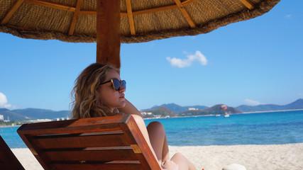 Beautiful woman in a bikini enjoys the tropical sun for a tan on a sunchair at a tropical beach in China