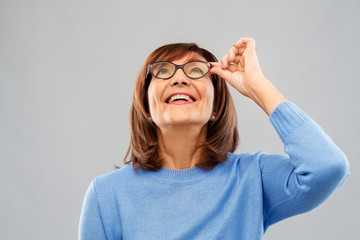 Fototapeta vision and old people concept - portrait of smiling senior woman in glasses looking up over grey background