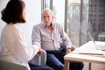 Female Doctor In Office Reassuring Senior Man Patient And Holding His Hands