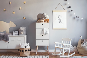 Scandinavian nursery room with mock up poster frame on the grey wall, white furniture, natural...