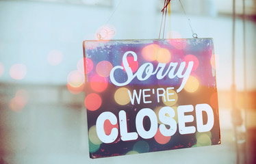 Closed sign hanging front of mirror door coffee shop double exposure with colorful bokeh light abstract background.