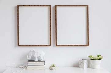 Stylish white home decor of interior with two brown wooden mock up photo frames on the white shelf with books, beautiful plant in stylish pot, elephant figure and home accessories.