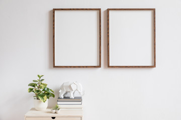 Stylish home interior with two brown wooden mock up photo frames above the wooden shelf with books, plants, and elephant figure. Modern concept of white room decor.