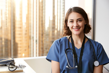 Portrait Of Smiling Female Doctor Wearing Scrubs With Stethoscope In Hospital Office