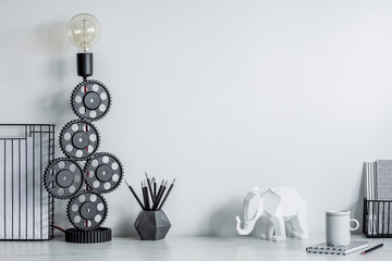 Modern and stylish black and white home decor mock up. Creative desk with blank picture frame or poster, desk objects, office supplies, elephant figure and design table lamp on a white background.