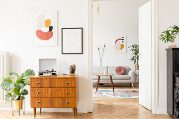 Stylish retro living room with design grey sofa, retro table, lamp and furniture. Mock up posters frame on the white walls. Minimalistic room with brown wooden parquet.