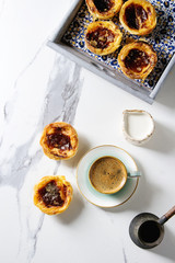 Traditional Portuguese egg tart dessert Pasteis Pastel de nata in classic tile tray with cup of black coffee and jug of milk over white marble background. Flat lay, space