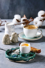 Breakfast with cup of coffee and soft boiled egg, served in green ceramic egg cup with salt, pepper and toasted bread, jug of cream and cotton flowers over grey blue table.