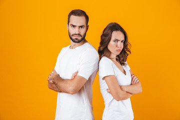 Photo of offended man and woman in quarrel standing back to back with arms folded, isolated over yellow background