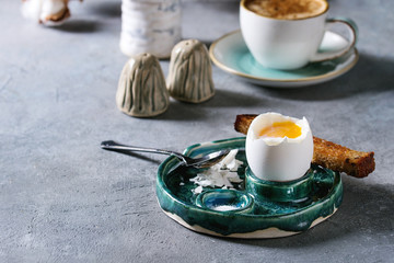 Breakfast with cup of coffee and soft boiled egg, served in green ceramic egg cup with salt, pepper and toasted bread, jug of cream over grey blue table.