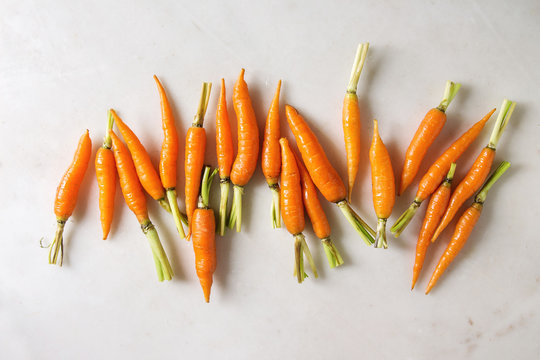 Young mini carrot in row over white marble background. Flat lay, space. Cooking concept, food background.