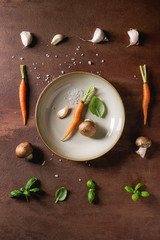 Fresh basil herbs with mini carrots and champignon mushrooms in row and in plate over brown background. Flat lay, space. Cooking concept, food background.