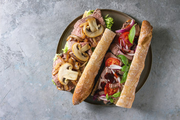 Variety of beef baguette sandwich with champignon mushrooms, green salad, tomatoes, fried onion served on ceramic plate over grey texture background. Flat lay, space
