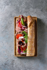 Beef baguette sandwich with tomatoes, basil, red onion served on wooden serving board over grey texture background. Flat lay, space