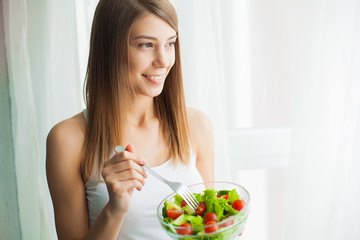 Diet and Healthy eating. Young woman eating healthy salad after workout