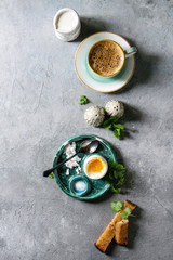 Breakfast with cup of coffee and soft boiled egg, served in green ceramic egg cup with salt, pepper and toasted bread, jug of cream over grey texture background. Flat lay, space