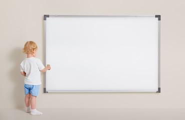 Little boy with paint brush standing near blank whiteboard