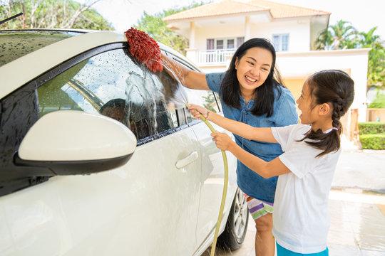 Happy asian little girl enjoy washing car