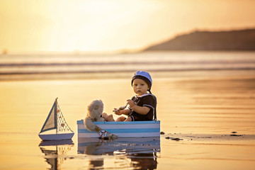 Cute baby child, sweet boy, playing with boat, teddy bear and fishes on sunset at the edge of the ocean