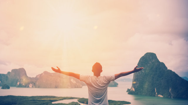 Feel good freedom and travel adventure concept. Copy space of happy man raise hands on  top of mountain with sun light abstract background.