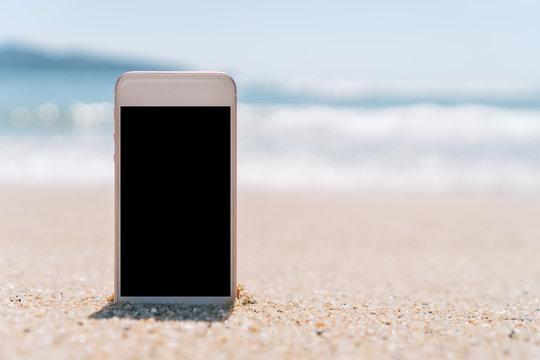 Smart phone on sand beach texture background.