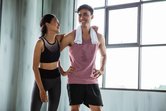 sport man and woman chatting in the gym after exercise together