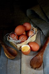 Many village eggs lie in a wicker basket in the chicken coop on the wooden floor.