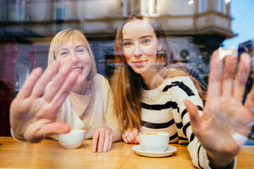 View through the window of blonde adult girl with her mature mother drinking coffee, they are sittting at cafe, waving you. Bonding, different generationsconnect, family concept.