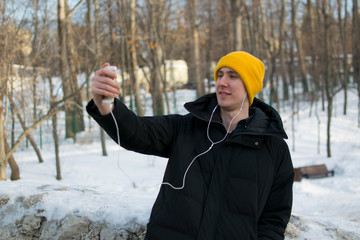 Portrait of a cheerful man taking selfie in the park