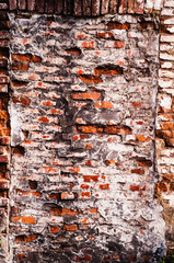 old bare wall with dirty cracked brickwork of red bricks and remnants of white plaster