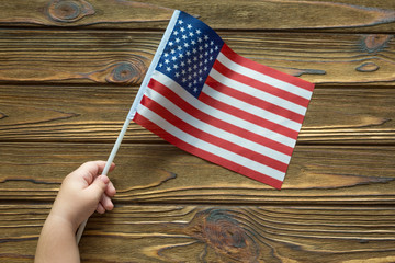 American flag in hand on wooden background. independence day holiday.