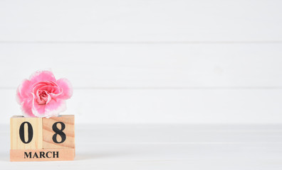 Womens day concept, happy womens day, international women's day. Pink carnation flower with March 8 text wooden calendar on white wooden background.