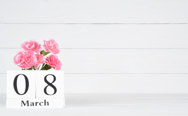 Womens day concept, happy womens day, international women's day. Pink carnation flower with March 8 text on wooden calendar on white wooden background.