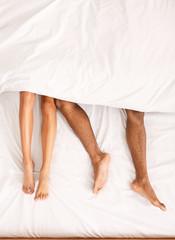 Obraz Male and female legs under duvet lying on bed - fototapety do salonu