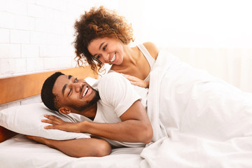 Happy couple flirting in morning on comfortable bed