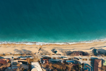 Scenic aerial view of golden sand waves and turquoise sea water with white foam from small waves. The concept of summer holidays. Bright abstract background perfect for any design.