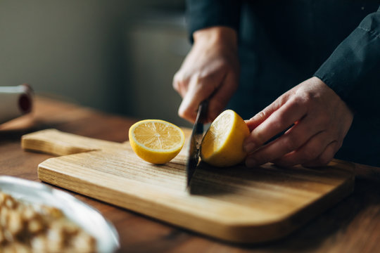 Chef cutting lemons on a wooden board