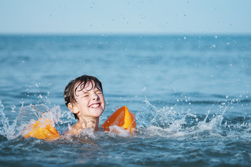 Happy smiling boy bathes in the sea near the shore with splashes of water. Wet hair. Orange inflatable swim sleeves. A child at the sea, rest in the summer, swimming in the sea. Summer school holidays